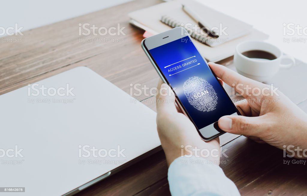 The hand is scanning biometric fingerprints for approval to access electronic devices. The concept of the danger of using electronic devices is important. stock photo