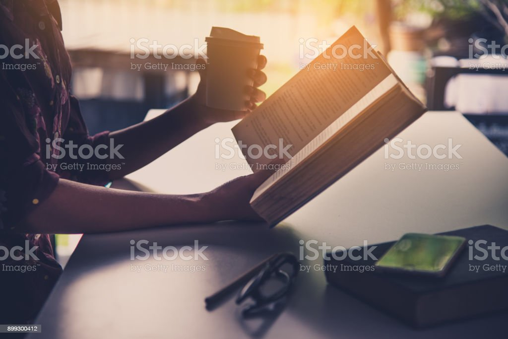 The hand of a businessman holding a cup of coffee and reading a book during leisure time. stock photo