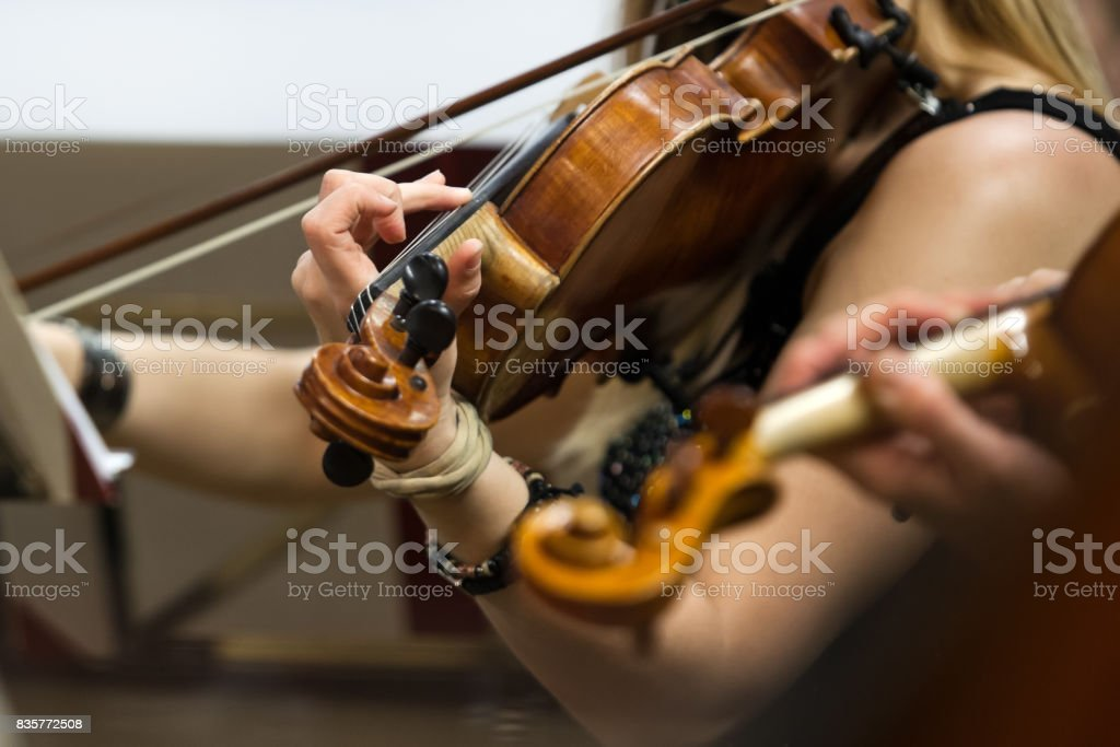 The hand of a girl playing the violin stock photo