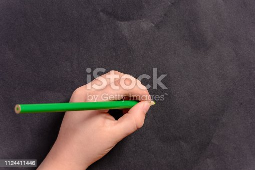 istock The hand of a little boy writes a pencil on a black background 1124411446