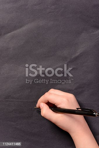 istock The hand of a little boy writes a pencil on a black background 1124411465