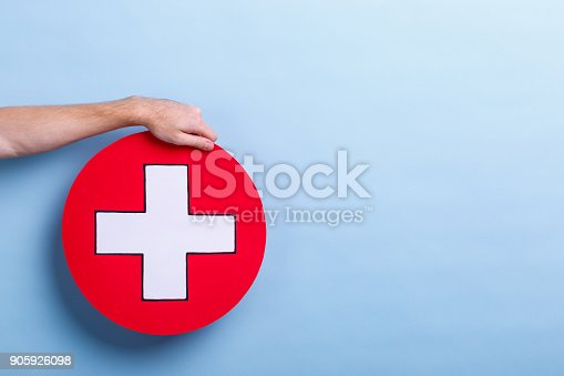 917079152istockphoto The hand of a man holds a medical sign, a cross in a circle. Blue background with a place for an inscription. 905926098
