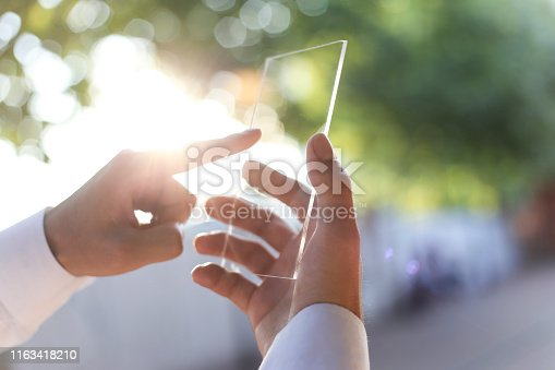 171347585 istock photo The hand of a man in suits, uses a futuristic glass phone with the latest advanced holographic technology. Concept of: future, technology, smartphone, augmented reality 1163418210