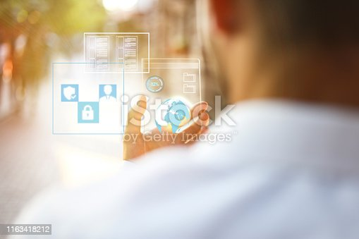 499253490istockphoto The hand of a man in suits, uses a futuristic glass phone with the latest advanced holographic technology. Concept of: future, technology, smartphone, augmented reality 1163418212