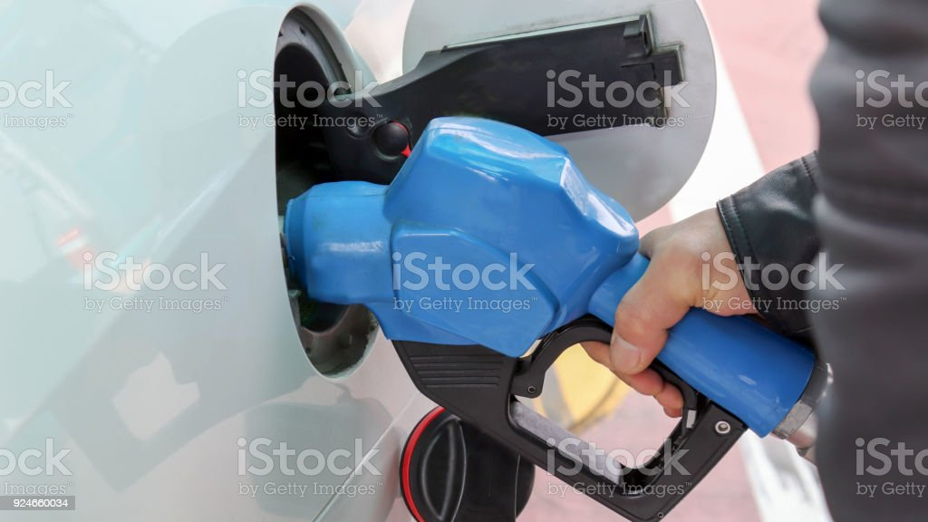 The hand of a man on gas. Pumping gas at gas pump. stock photo