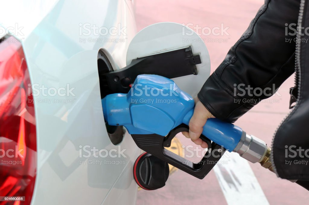 The hand of a man self-fueling at a gas station. stock photo