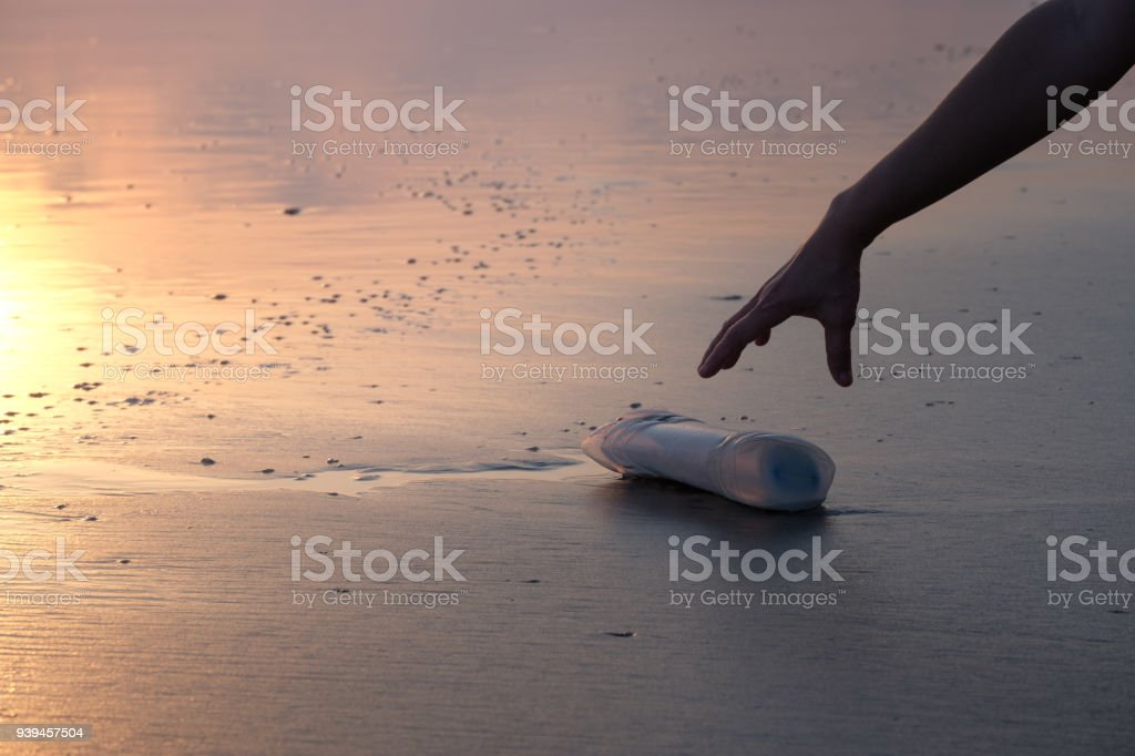 The hand of a woman is picking up a plastic bottle royalty-free stock photo