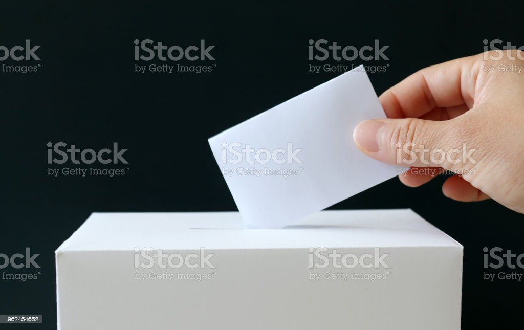 The hand of a woman putting a ballot in the ballot box. Close-up image of ballot and the ballot box. stock photo