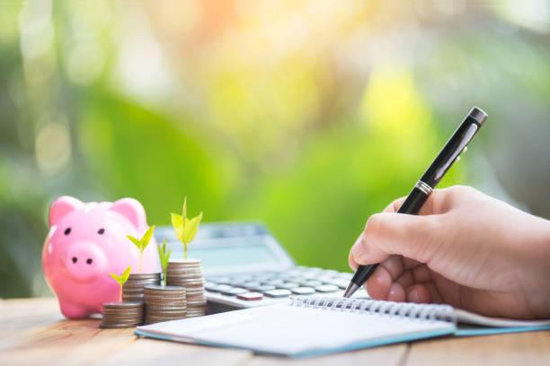 la mano de una mujer que está registrando la alcancía de planificación financiera para dar un paso adelante en el negocio para obtener beneficios y ahorrar con la alcancía, - planificación financiera fotografías e imágenes de stock