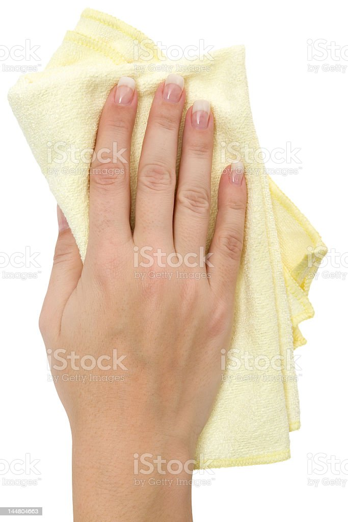 The hand of a woman with a yellow cloth wiping the wall stock photo