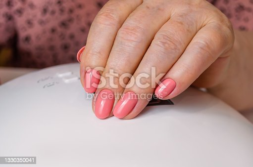 istock The hand of an adult woman with a beautiful pink manicure on the background of a lamp. The nails are covered with gel polish. 1330350041