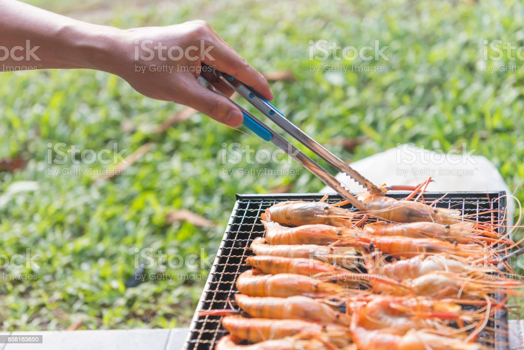the hand of chef choose the grill shrimp stock photo