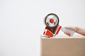 istock The hand of the child seals the cardboard boxes with a dispenser and adhesive tape. 1133549985