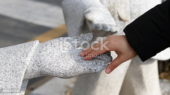 istock The hand of the woman holding a stone statue's hand 899052340