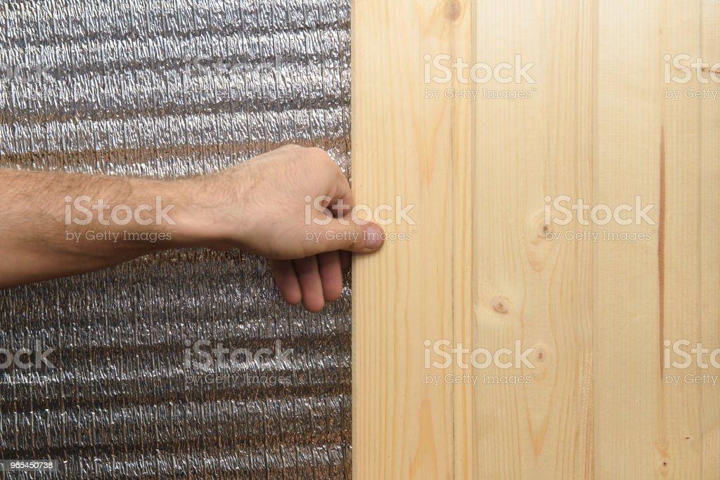 工人的手上覆蓋著一塊鑲有箔片的木板牆。 - 免版稅乾的圖庫照片
