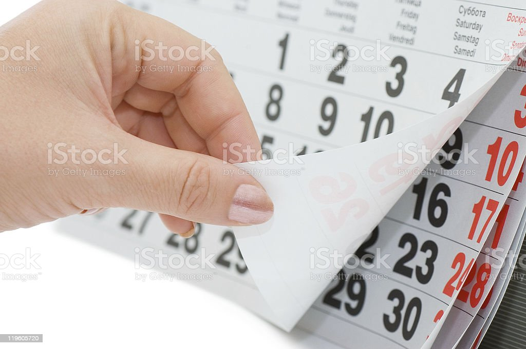 The hand overturns calendar sheet isolated on white background stock photo