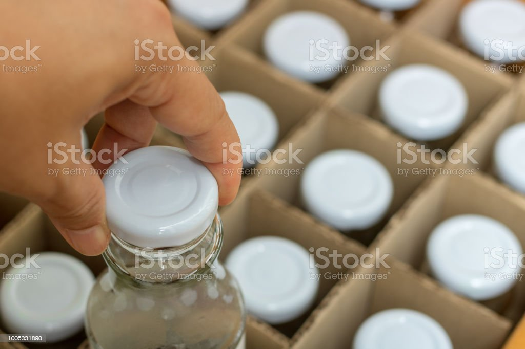 The hand picking a glass bottle with white bottle caps in a cardboard...