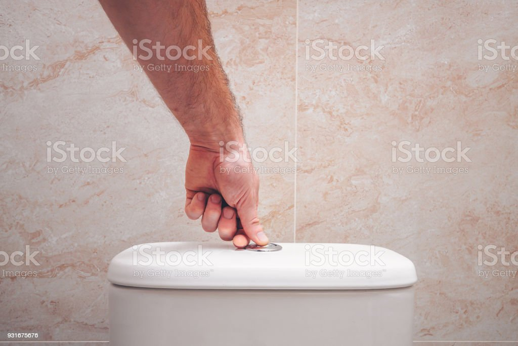 The hand presses the button on the toilet bowl, the economical drain stock photo