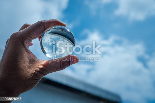 The hand was holding a glass ball and shone at the blue sky.