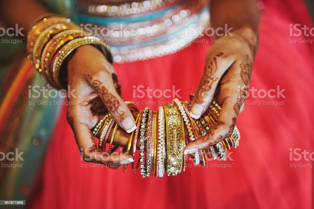 The hand with mehndi of Indian bride holding a lot of glitter bracelets (bangle) with red legenha background, close-up stock photo