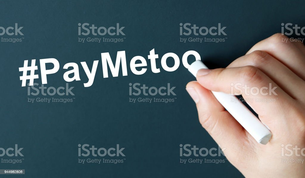 The hand writing text #PayMeToo in white chalk. A campaign to close the gender pay gap. stock photo