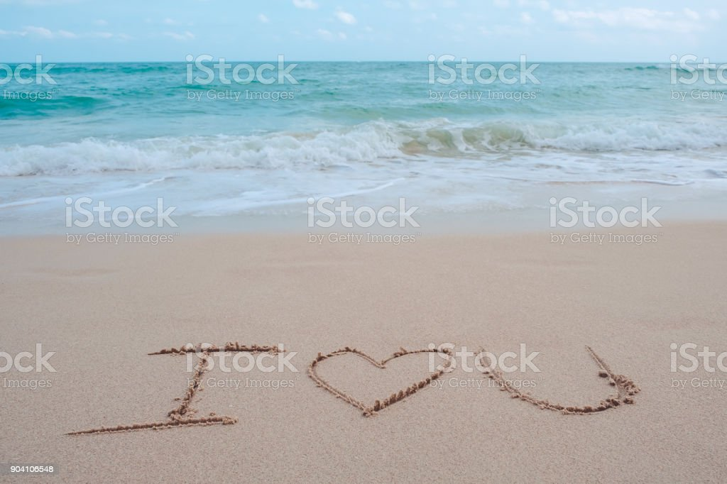 The hand writing word I love you on the beach by the sea with white waves and blue sky background stock photo