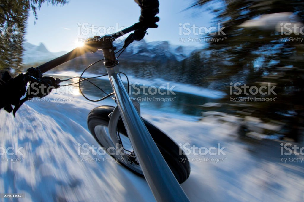 The handlebar view of a man on a winter fat bike ride in the Rocky Mountains of Alberta, Canada. stock photo