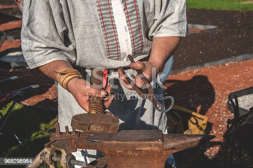 istock The hands of a blacksmith forging metal parts on the old anvil over an open fire. Folk craft 968298984