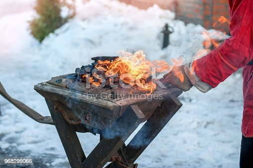 istock The hands of a blacksmith forging metal parts on the old anvil over an open fire. Folk craft 968299066