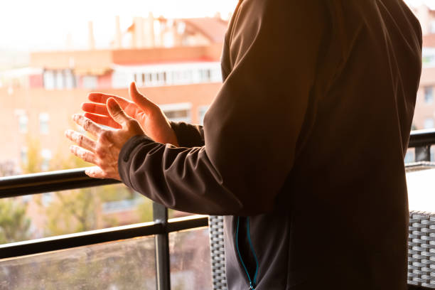 The hands of a man clapping from his balcony in Spain to support medical staff due coronavirus pandemic stock photo