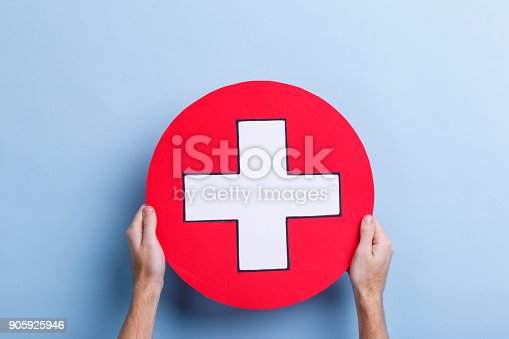917079152istockphoto The hands of a man hold a medical sign with both hands, a cross in a circle. 905925946
