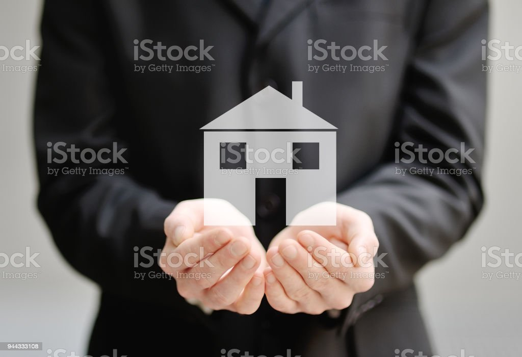 the hands of a man holding a house - insurance and protection concept stock photo