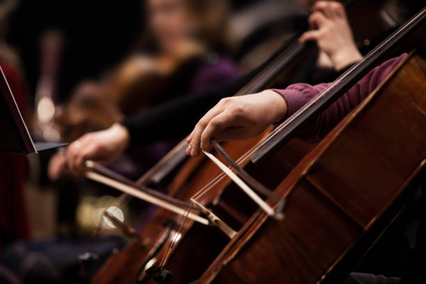 The hands of a musician playing the cello The hands of a musician playing the cello in an orchestra in dark tones classical style stock pictures, royalty-free photos & images