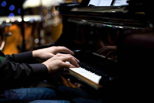The hands of a musician playing the piano The hands of a musician playing the piano closeup in dark tones pianist stock pictures, royalty-free photos & images