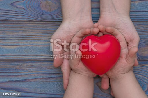 823097608istockphoto the hands of an adult and a child are held in the red heart, health insurance, family insurance, 1157175668