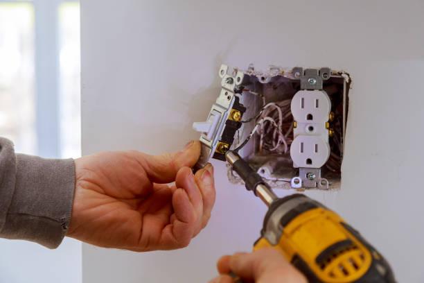 las manos de un electricista instalando un interruptor de encendido - electricity fotografías e imágenes de stock