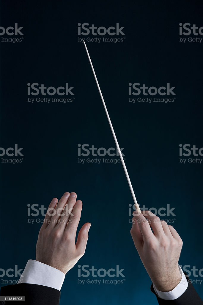 The hands of an orchestra conductor holding up a baton stock photo