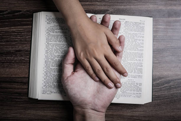 The hands of child and man on the holy bible The hands of child and man on the holy bible. clergy stock pictures, royalty-free photos & images