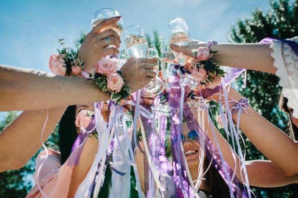 Les mains des filles avec des boutonnières et des rubans tiennent et soulèvent des verres de Champagne vers le haut. verre de Champagne décoré de fleurs. Fête dans le style Boho. Soirée de poule Party. Bachelorette. Gros plan - Photo