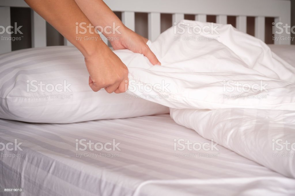 The hands of housewives who are changing sheets in hotels.