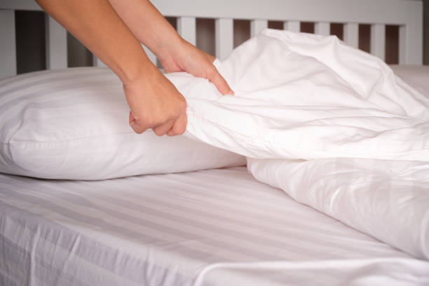 The hands of housewives who are changing sheets in hotels. stock photo