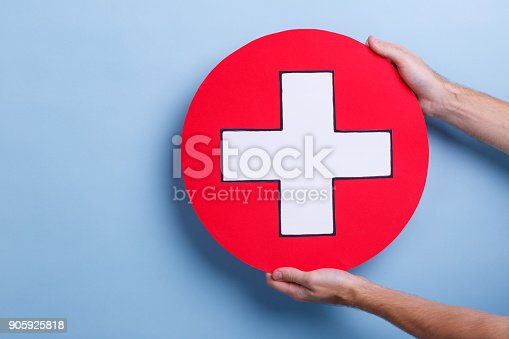 917079152istockphoto The hands of man hold a medical sign, a white cross in a red circle. Blue background. 905925818