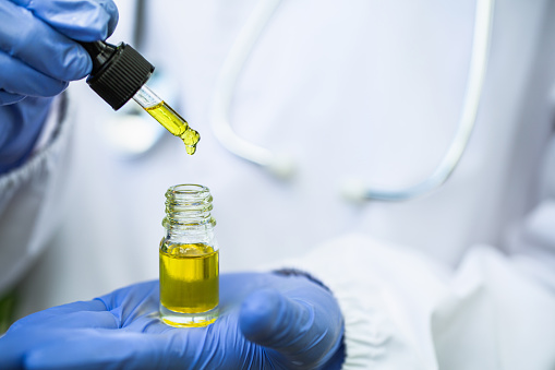 1177762728 istock photo The hands of scientists dropping marijuana oil for experimentation and research, ecological hemp plant herbal pharmaceutical cbd hemp oil from a jar. 1249308727