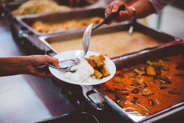 Die Hände der Bettler, die von Freiwilligen unterstützt wurden, boten leckeres Essen an: das Konzept der Armut. – Foto