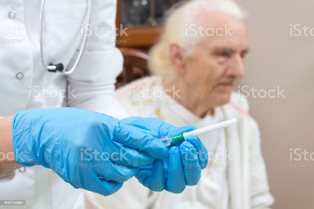 The hands of the doctor in gloves prepare the injection. An old gray sick woman is sitting on a chair in the background. stock photo