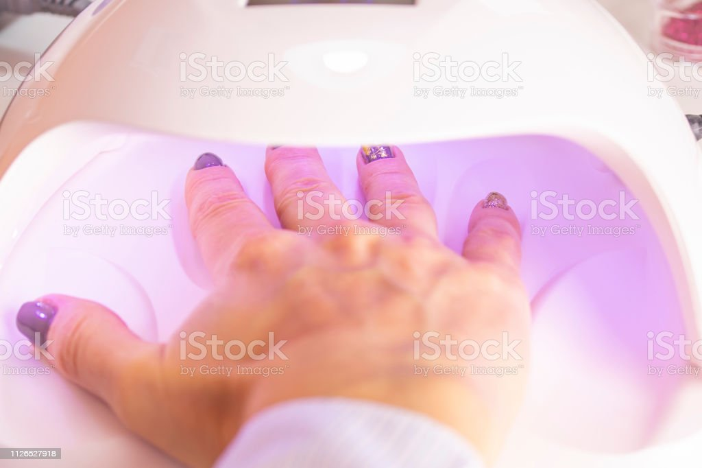 The Hands Of The Girl In The Uv Lamp For Nails On The Manicure Table Stock Photo Download Image Now Istock