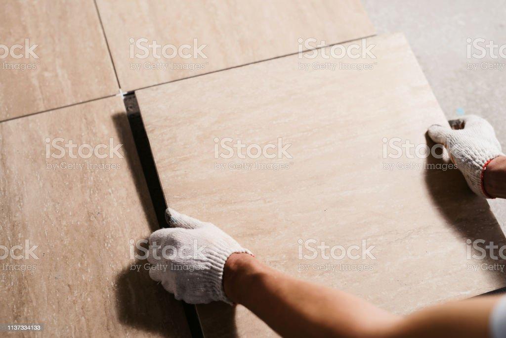 As mãos do Tiler estão colocando a telha cerâmica no chão. Feche acima do tiro macro. Renovação Home e conceito novo da casa do edifício - Foto de stock de Adulto royalty-free