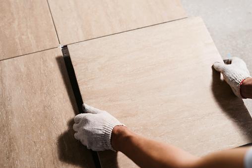 Foto de As Mãos Do Tiler Estão Colocando A Telha Cerâmica No Chão Feche Acima Do Tiro Macro Renovação Home E Conceito Novo Da Casa Do Edifício e mais fotos de stock de Adulto