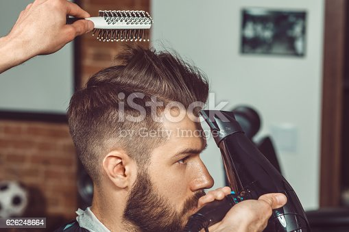 istock The hands of young barber making haircut to attractive man 626248664