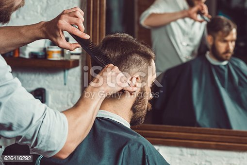 istock The hands of young barber making haircut to attractive man 626416292
